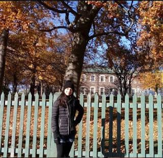 menina em frente a uma cerca verde