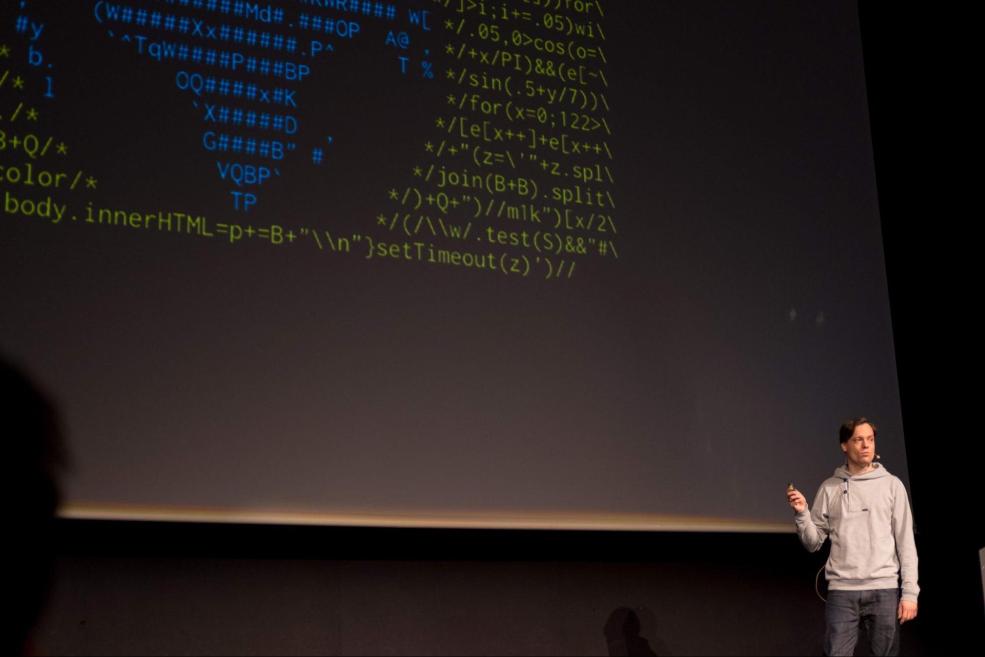 Image shows Martin Kleppe presenting onstage. A large projector screen displays code behind him