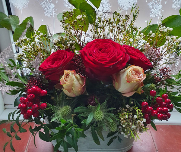 Christmas Centerpiece flower arrangements made with red and cream coloured roses and green folage