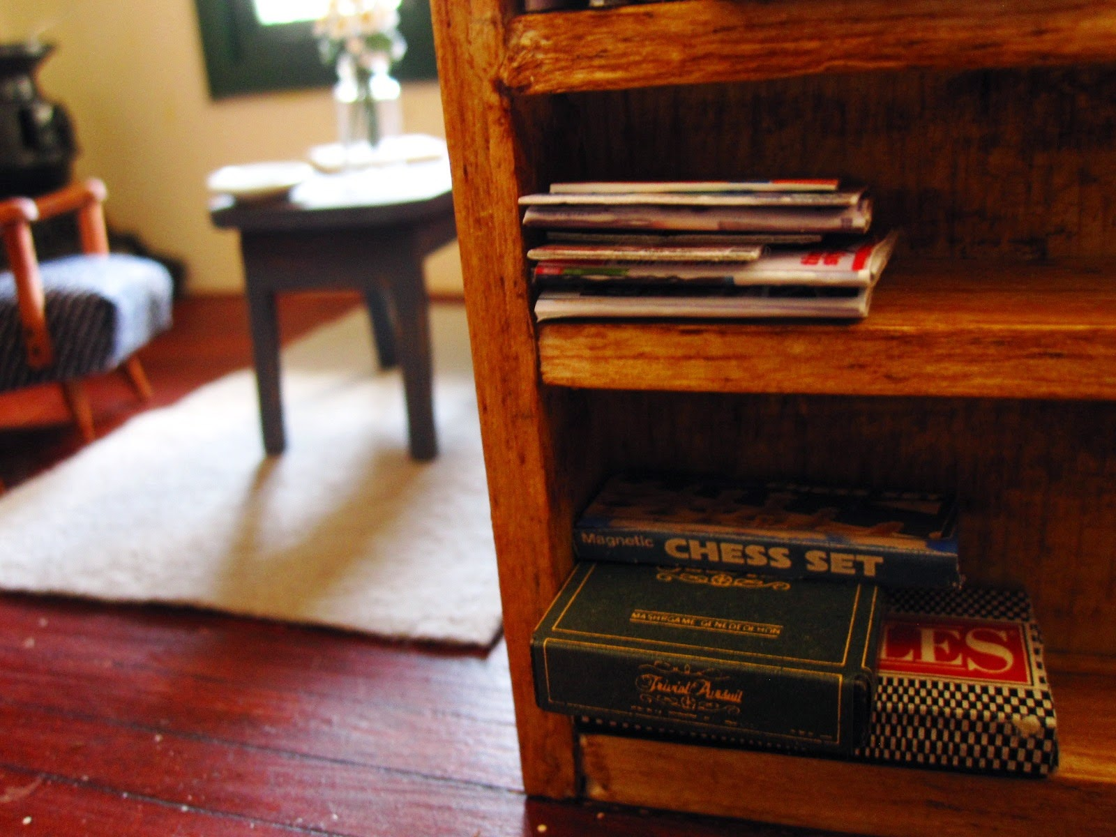 Dolls house miniatrie bookcase with a stack of game boxes on the bottom shelf.