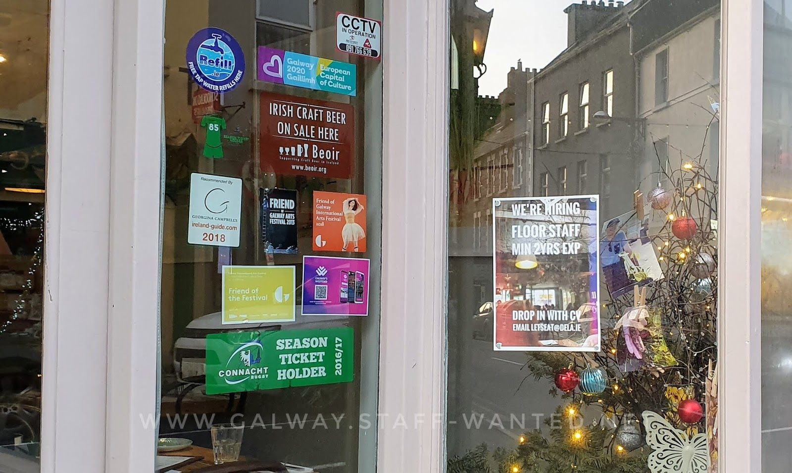 job add in front of Christmas decorationns - shopfront also has stickets for Connacht rubgy season ticket holder, and craft-beef available in this restaurant