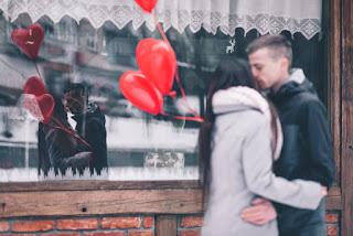 Pareja besándose en san Valentín con globos rojos