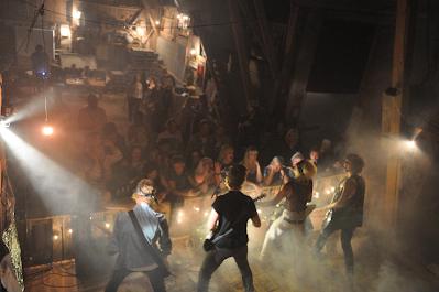 Band som spelar på inomhusscen sett bakifrån scen med publik i bakgrunden.