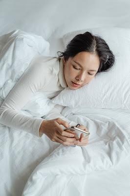 Mujer recostada en una cama, revisando sus redes sociales.