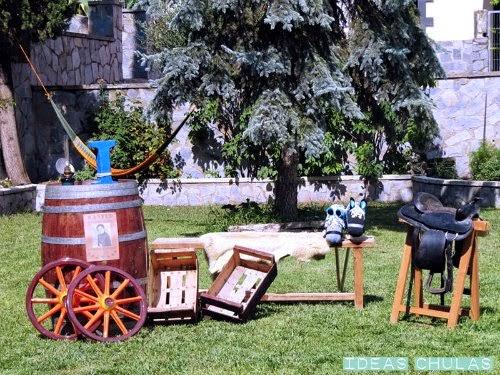 Photocall far west, con un barril, un banco, cajas, una silla de montar sobre un caballete