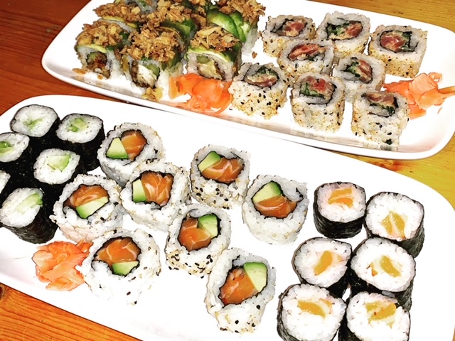 Two platters, consisting of a variety of sushi rolls with salmon, tuna and avocado
