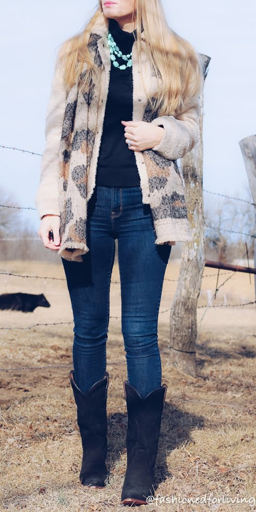 women black cowboy boots outfit with skinny jeans, teddy coat, and leopard scarf