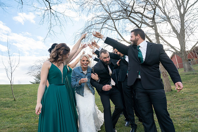 Bridal party making an arch holding their hands up while Bride and Groom go under the arch Magnolia Farm Asheville Wedding Photography captured by Houghton Photography