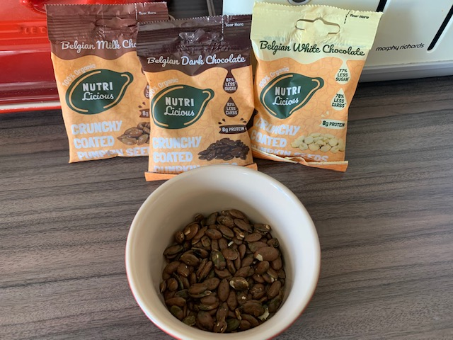 Three packets of chocolate covered pumpkin seeds