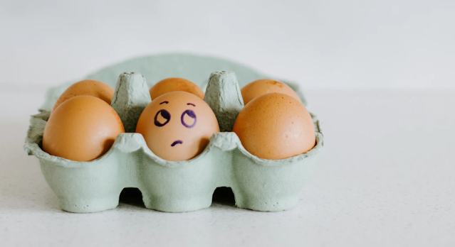 A box of eggs with eyes drawn on