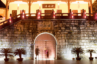 Mysterious figure standing at a gate in Guilin, China. Nighttime image with colored lights.