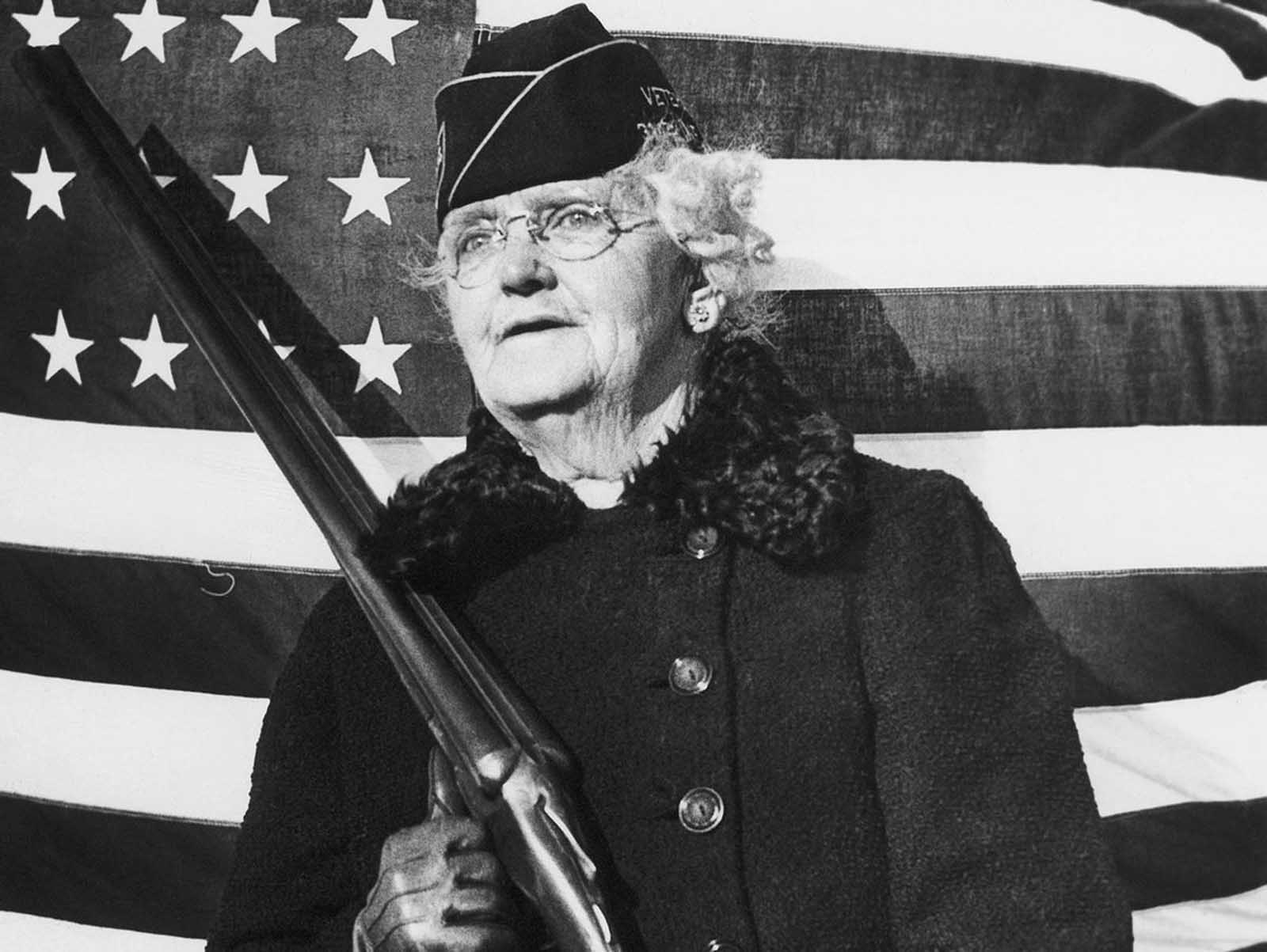 Mrs. Paul Titus, 77-year-old air raid spotter of Bucks County, Pennsylvania, carries a gun as she patrols her beat, on December 20, 1941. Mrs. Titus signed-up the day after the Pearl Harbor attack.