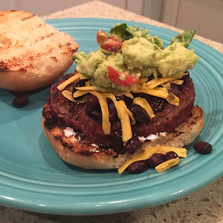 Mexican Taco Burgers topped with black beans, cheese, sour cream & guacamole.  Grill them on Big Green Egg (or grill of choice) Delicious! | The Lowcountry Lady