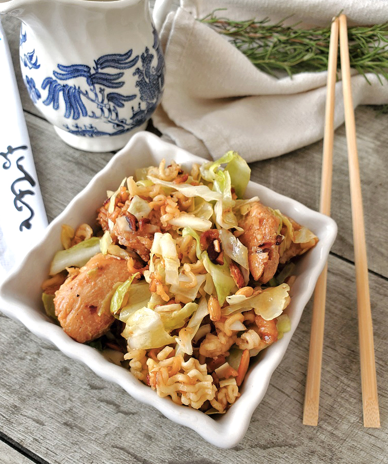 this is an oriental chicken salad in a square white dish with chopstick