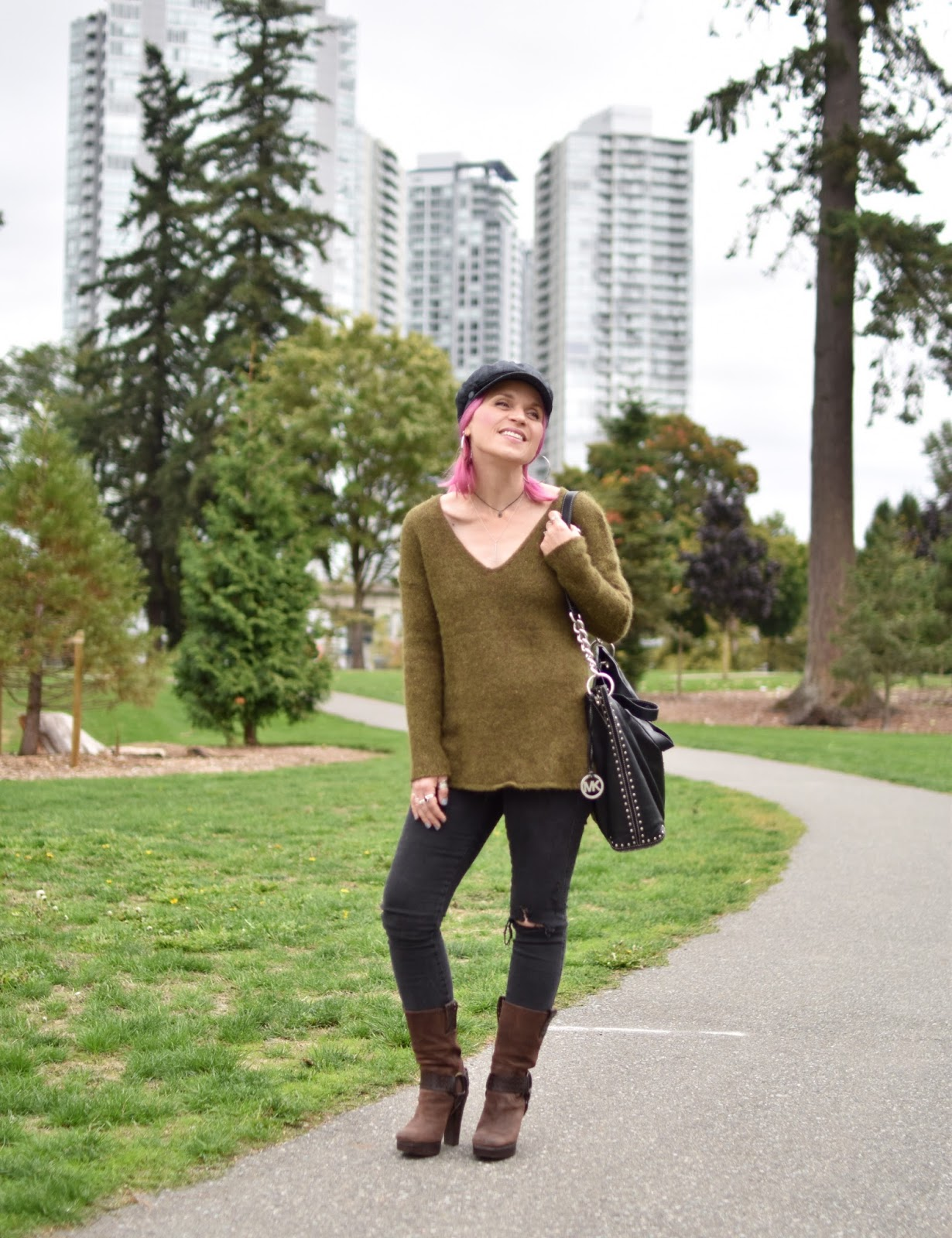 Monika Faulkner outfit inspiration - tunic sweater, distressed skinny jeans, platform harness boots, baker boy cap