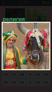 около животного с признаками религии стоит мужчина пожилой