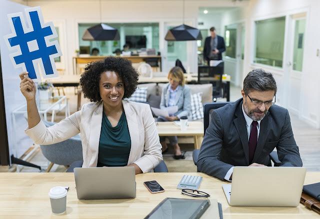 seorang wanita yang sedang bekerja di depan laptop dan memegang simbol hashtag