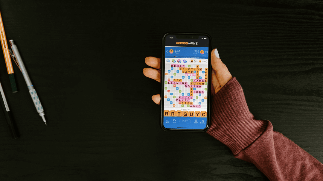 Woman holding phone playing Words with Friends