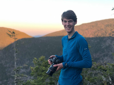 A photo of me, Ethan Rambacher, camera in hand, on Noon Mountain at sunset.