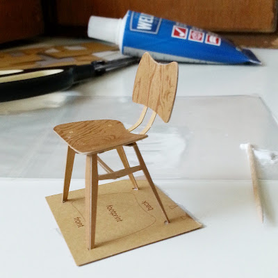 Almost completed cardboard model of a 1958 Ercol butterfly chair, set in a jig in front of the tools used to make it.