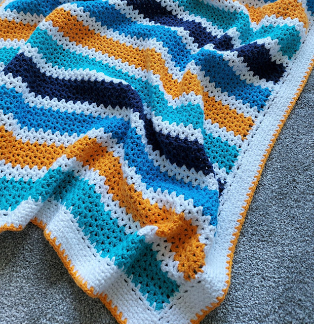 A cute stripy crochet v-stitch baby boy blanket