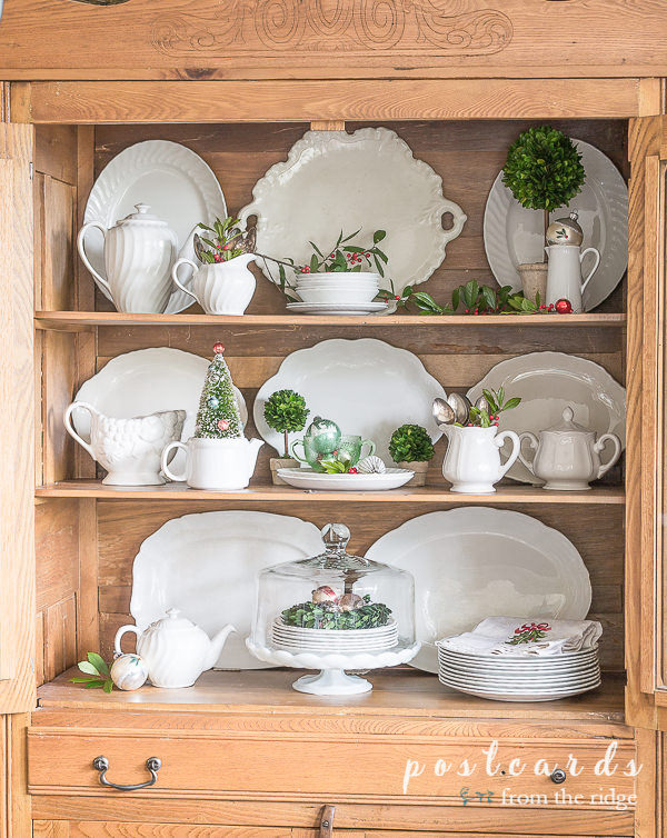 vintage white ironstone and christmas ornaments in antique oak hutch