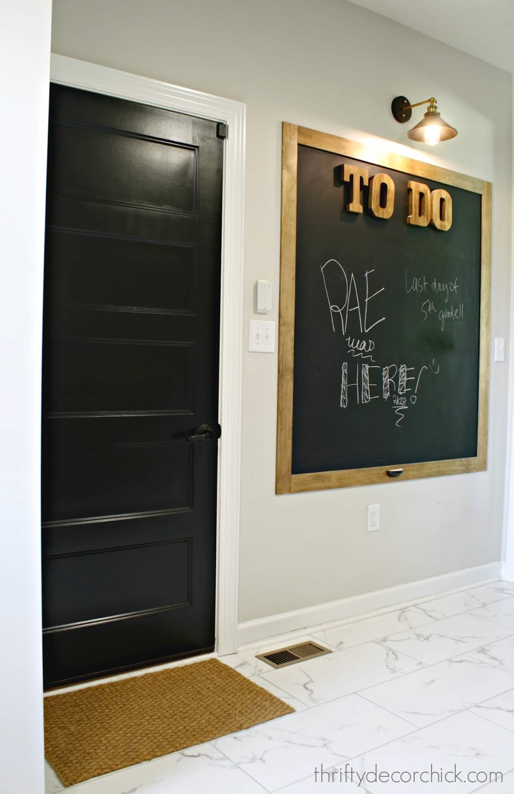 Black interior door with light marble tile