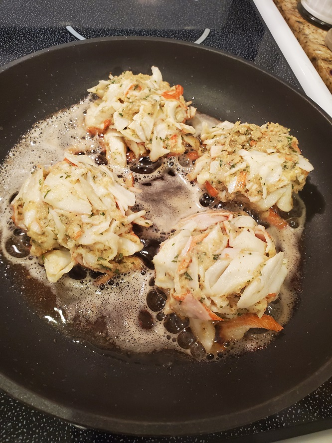 these are crab cakes starting to brown in a large frying pan