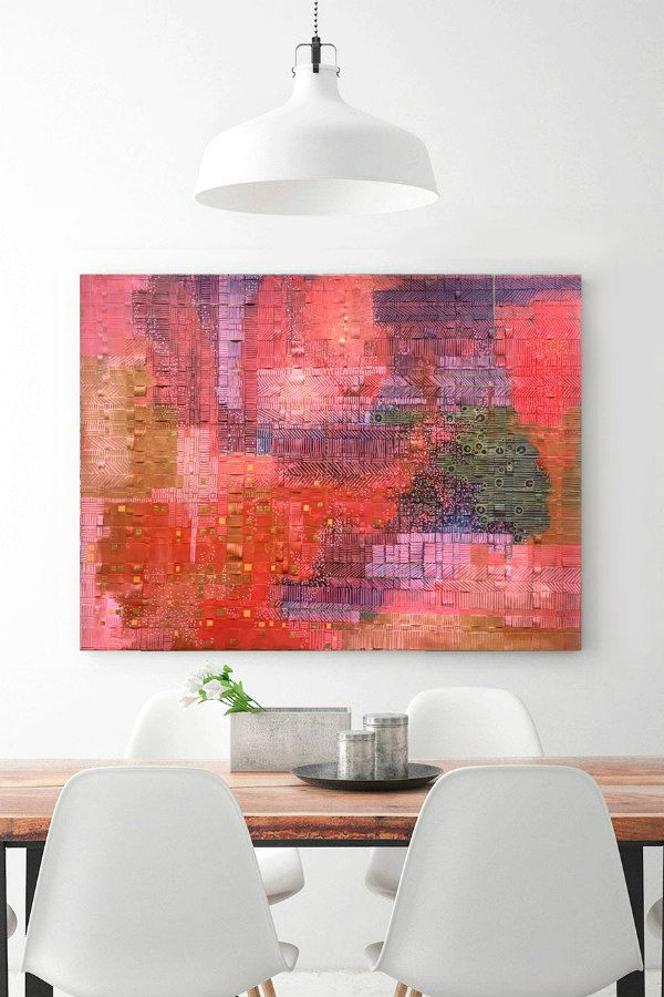 pink, red, purple, green, and gold woven paper wall art hanging above wood table and white chairs
