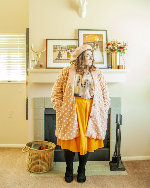 An outfit consisting of a pastel pink beret, a pink knee length pom pom coat over a white sweater tucked into a yellow midi skirt and black ankle boots.