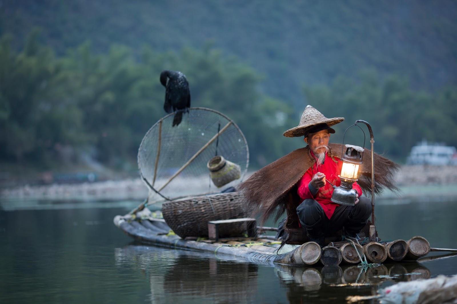 người đàn ông bắt cá với chim cốc trên con sông màu lam chiều nhìn như tranh thủy mặc