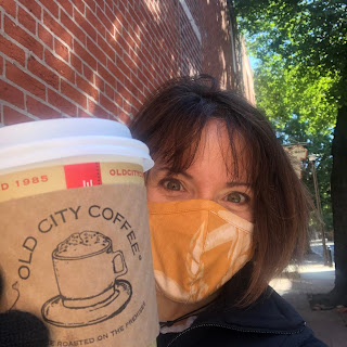 A selfie of me, wearing a mask, with a carry out coffee cup from Old City Coffee.
