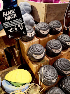 A group of spherical black bath bombs with a white middle in a square light brown rectangular box with a black rectangular tabel that says black ninja in white font on a bright background