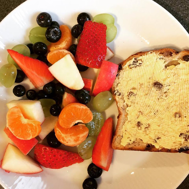Fruit salad on a plate with a slice of fruit loaf