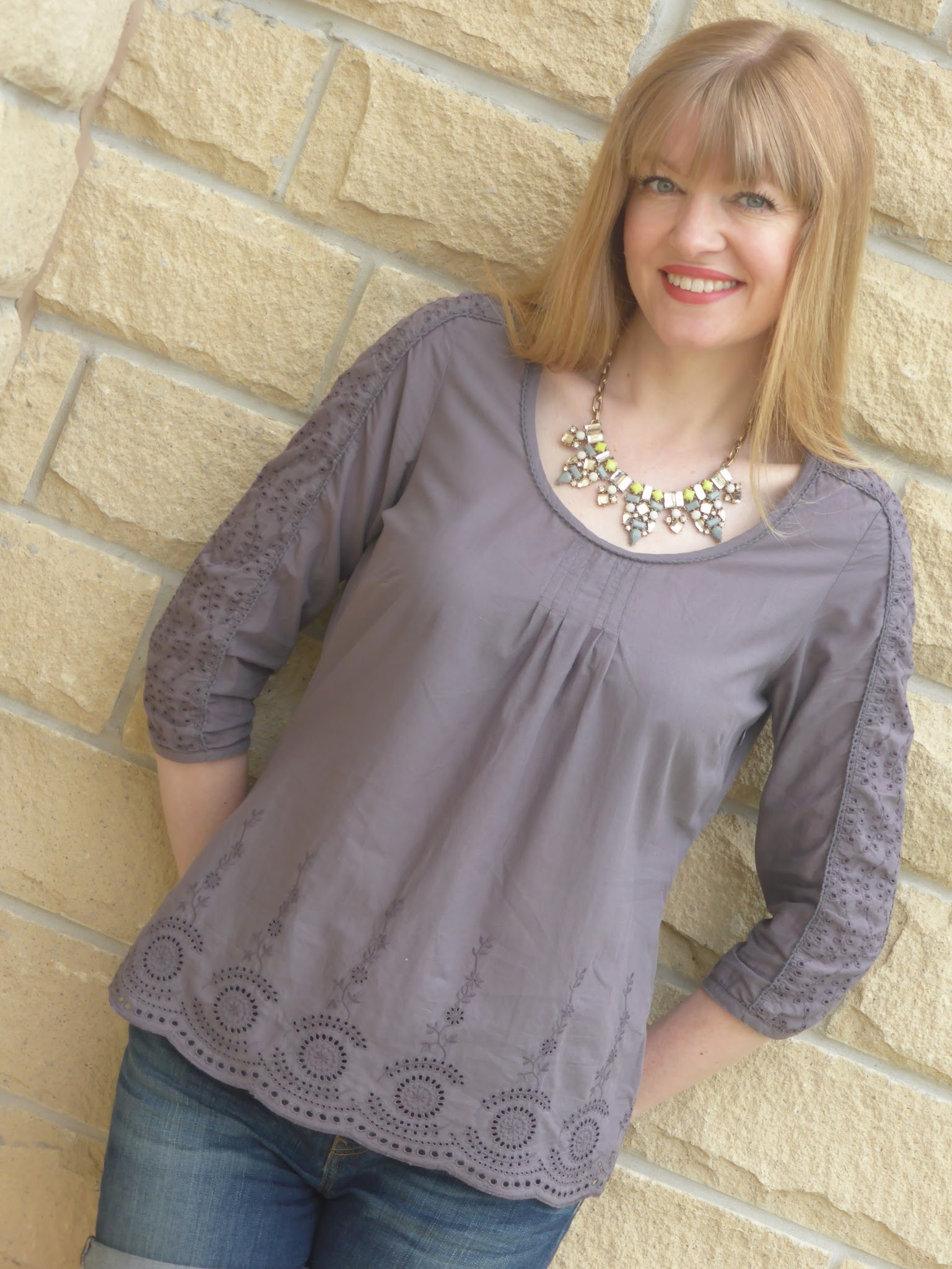 Over 40 blogger What Lizzy Loves wears grey broderie top, denim shorts and grey and yellow statement necklace