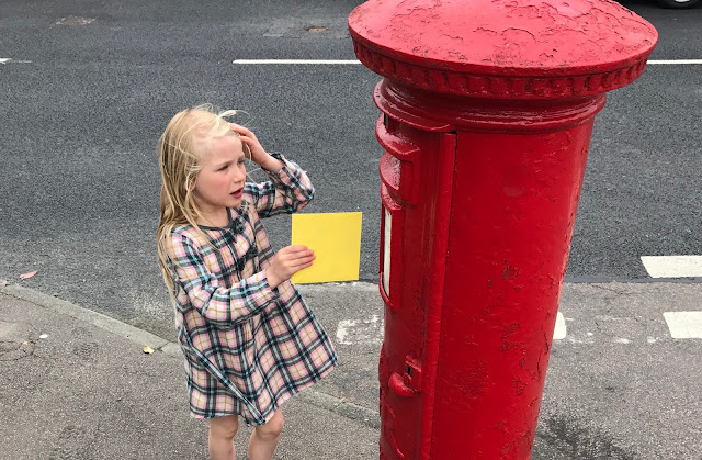 M is standing in front of a red letter box with a yellow envelope in her hand ready to post the letter