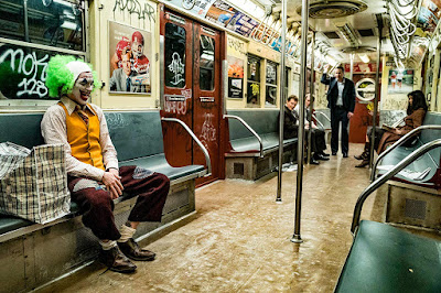 "Arthur Fleck (Joaquin Phoenix) sits on the New York City subway in his clown costume in a movie still for ""Joker"" (2019)"