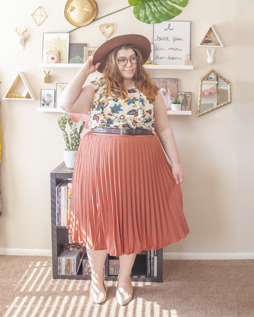 An outfit consisting of a brown wide brim hat, a cream sleeveless dress with vertical ruffles with a jewel tone floral print tucked into a rose pleated midi skirt and beige pointed slingback heels.