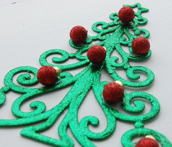 green christmas tree ornament with small red glitter bulbs upclose