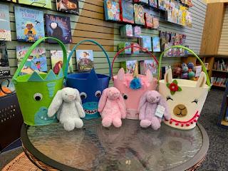 four felt animal face Easter baskets sit on a table with three plush bunnies