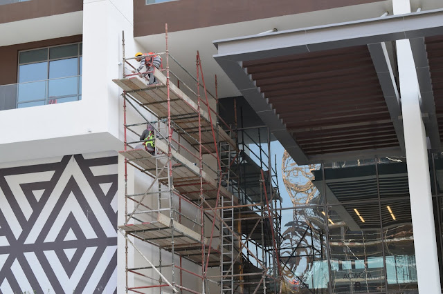 Construction workers on a scaffold working on a wall
