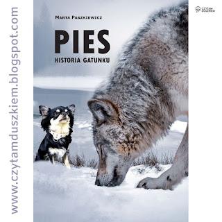 """Okładka książki Marty Paszkiewicz pt. """"Pies. Historia gatunku"""" - na śniegu szczeniak z dorosłym psem"""