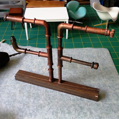 One-tweltfh scale modern miniature pipe shelving mounted on a length of wood , on a workbench next to a drill.