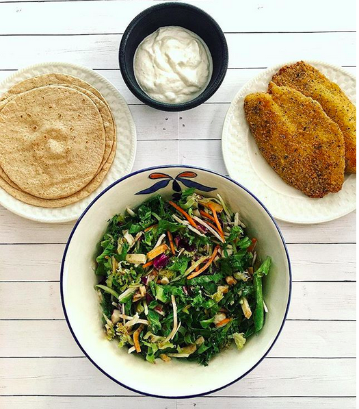 white table, wheat tortillas, breaded tilapia, salad in a bowl