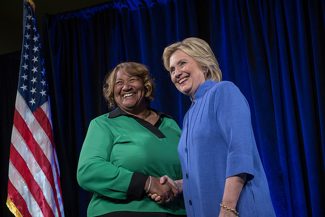 image of a middle-aged fat Black woman posing for a picture with Hillary as they shake hands