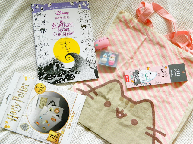 A photograph showing Harry Potter stickers, a Nightmare Before Christmas colouring book, a Pusheen the cat tote bag with pink and white stripes