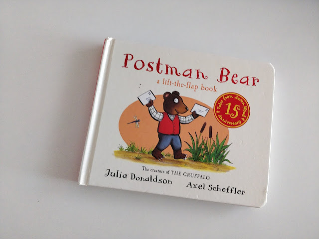 "A book sits on a white surface. The cover says Postman Bear in large red lettering. Below it says ""a lift-the-flap book"" in the same red. An illustration of a bear holding up letters as he walks along a path with a few green plants around and an orange oval as the background. The bottom has text that reads ""The Creators of THE GRUFFALO"" Underneath reads Julia Donaldson to the left with Axel Scheffler to the right."