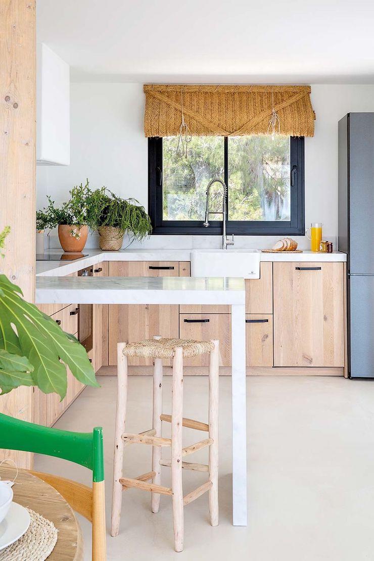 cocina de estilo mediterráneo con muebles de madera y cortina de esparto.