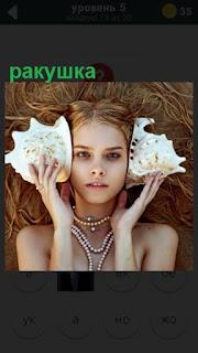 девочка в руках держит две ракушки которые приложила к ушам