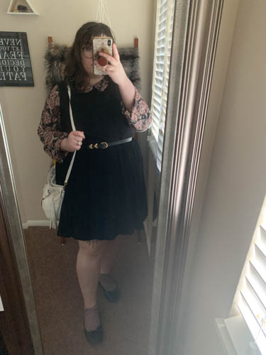 A mirror selfie of an outfit of a pink, black and purple paisley Peter Pan collared dress layered under a sleepless black dress, pink marled socks, and black ballet flats.